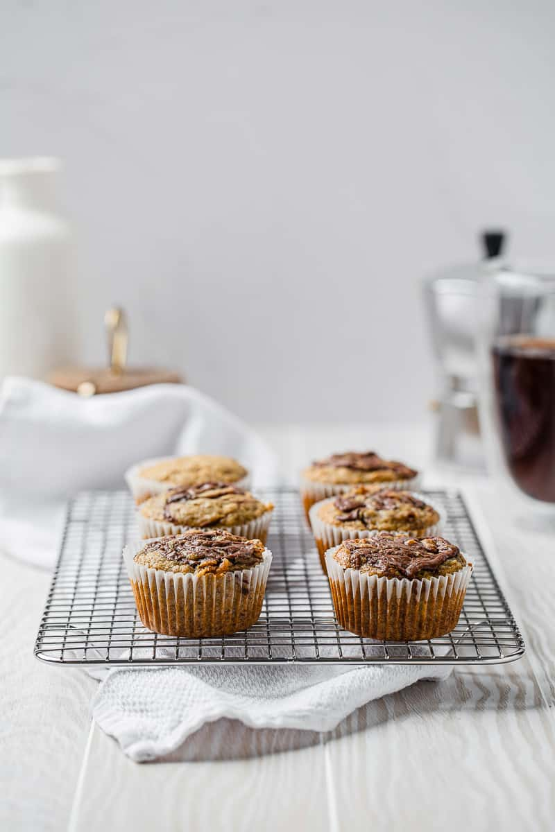 banana nutella muffins on a cooling rack with coffee in the background