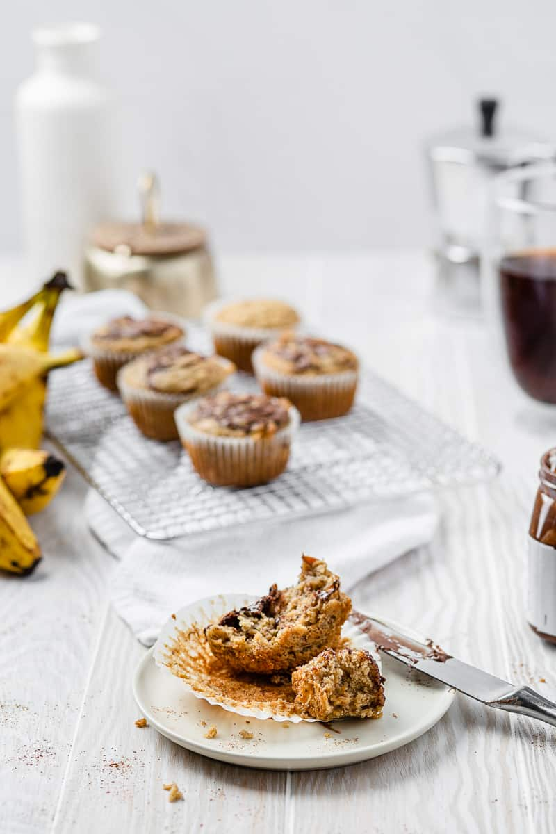 bananas in the background and a muffin on a plate