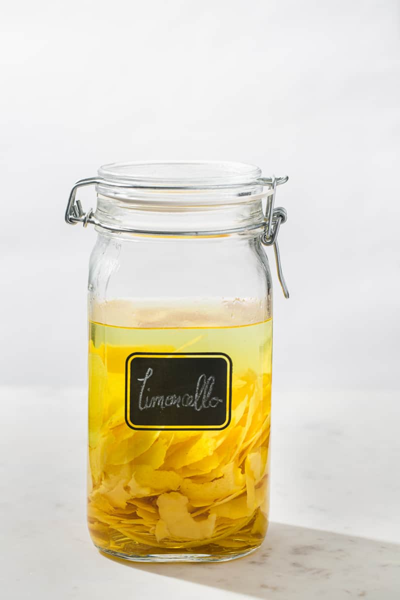 glass jar filled with vodka and lemon peels with a handwritten limoncello label