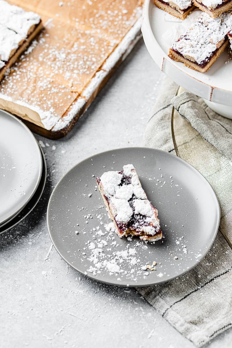 raspberry linzer bar with a bite taken out of it on a plate