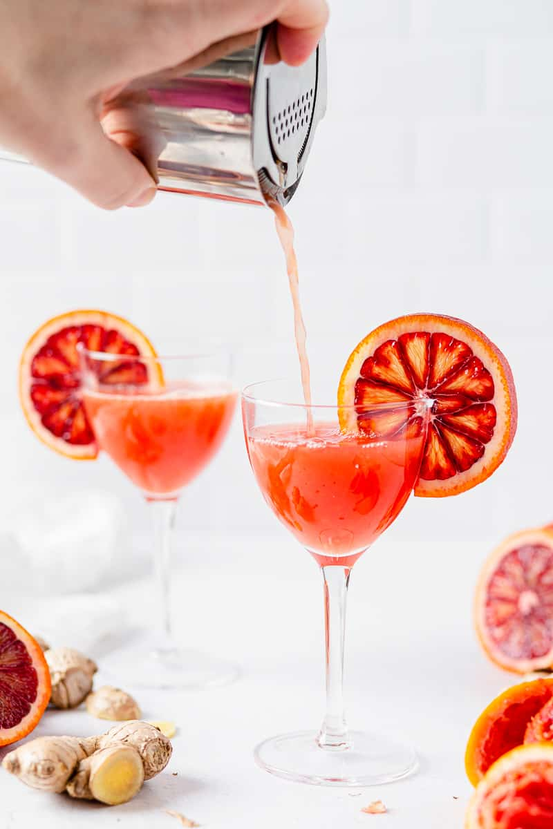 pouring blood orange cocktail into glass