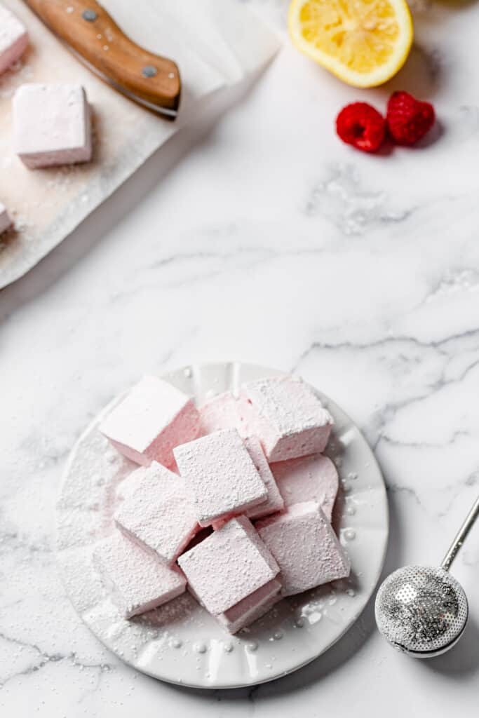 overhead shot of homemade marshmallows on a plate with a juiced lemon and raspberries