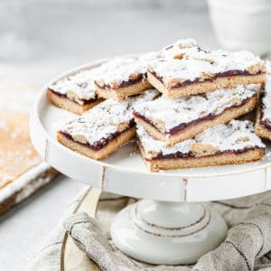 raspberry linzer bars in a pile on a cake plate