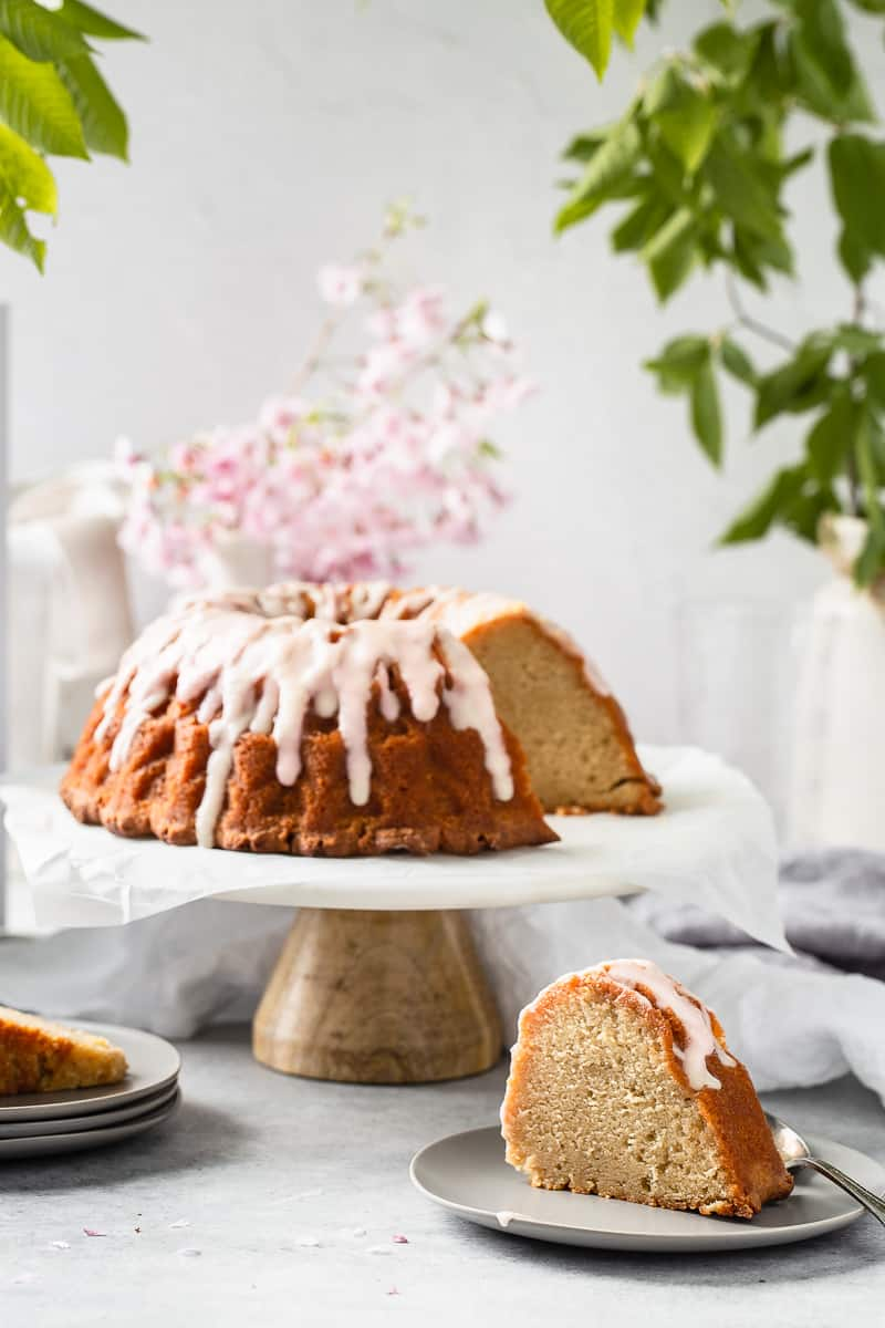 slice of vanilla buttermilk pound cake on a plate with the full cake on a cake stand