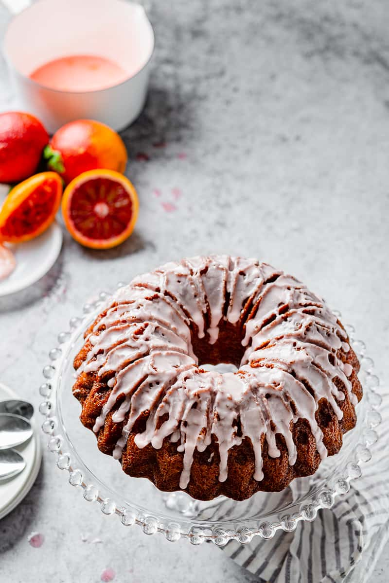 blood orange pound cake on a cake stand with blood oranges in the background