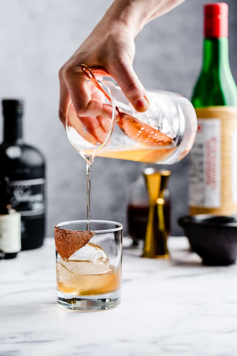 pouring mezcal cocktail over a sphere of ice