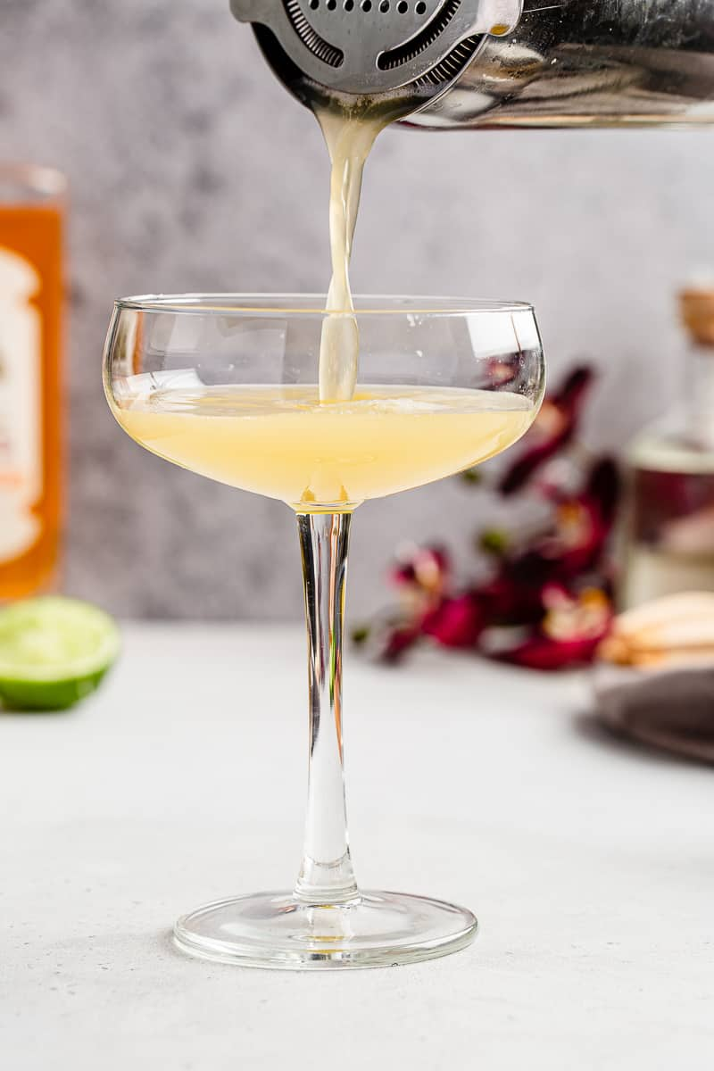 pouring passionfruit mango sour into a coupe glass