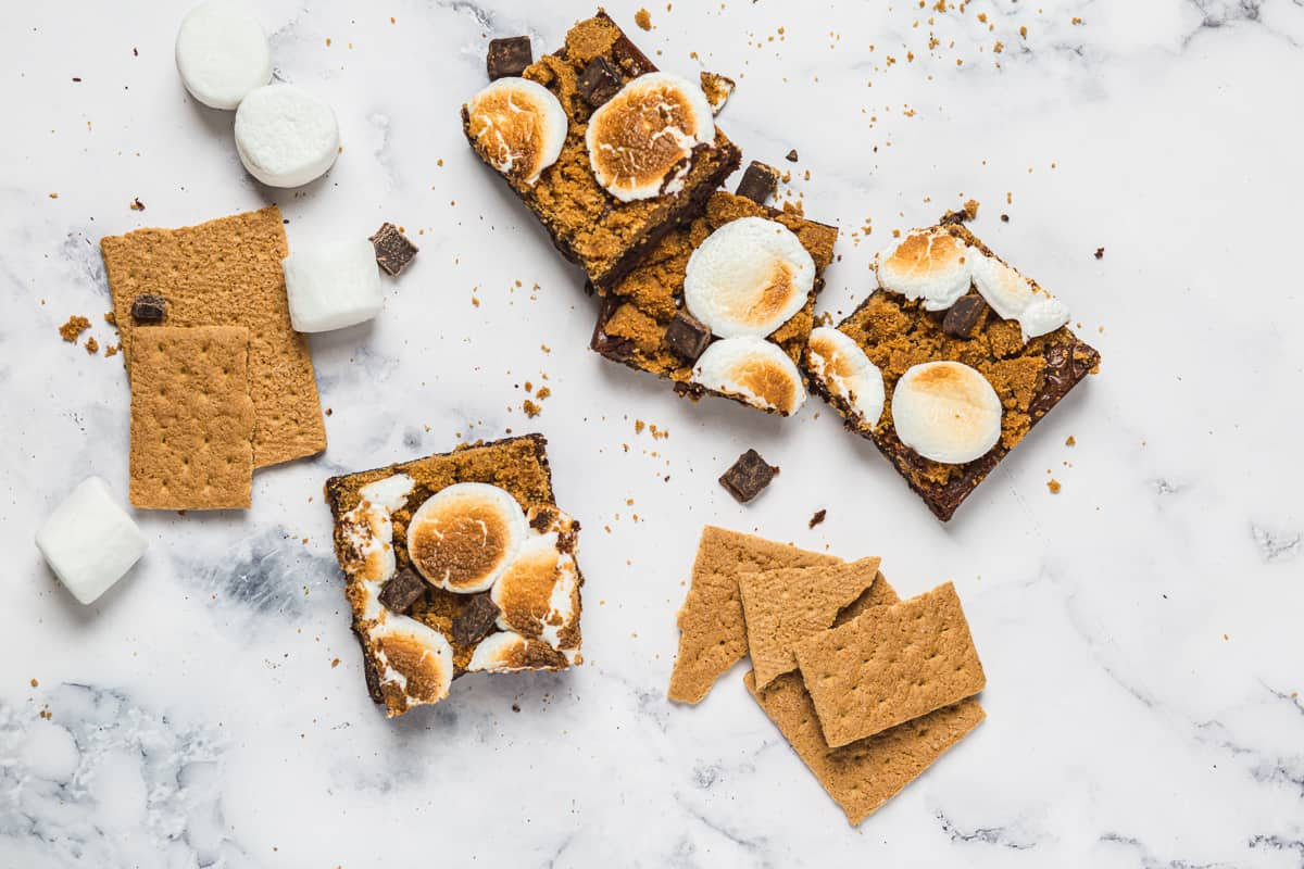 smores brownies with graham streusel, with graham crackers and marshmallows strewn about