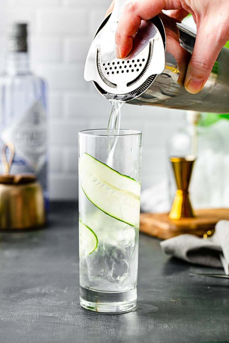 pouring cocktail into glass with cucumber strip inside
