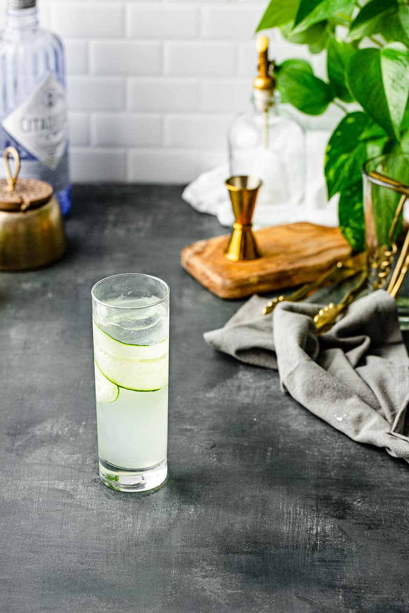 top view of cucumber gin cocktail with jigger and tongs in background