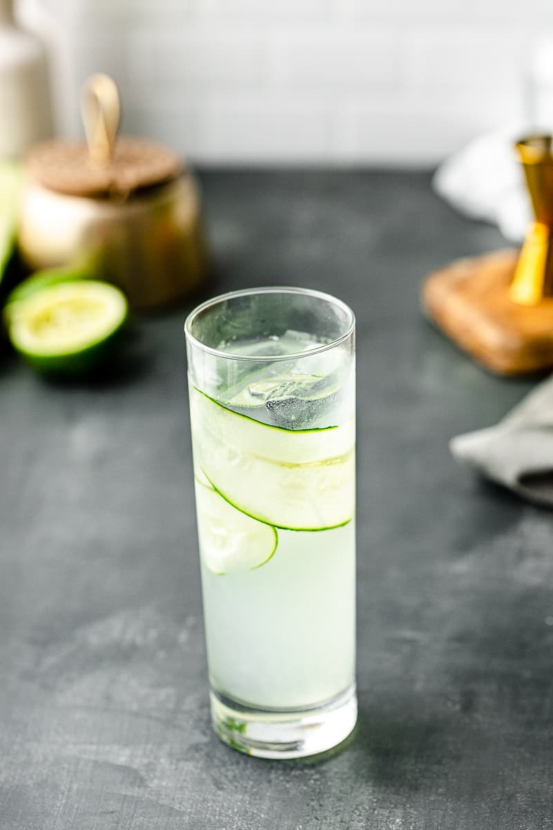top view of cucumber gin cocktail with lime in background