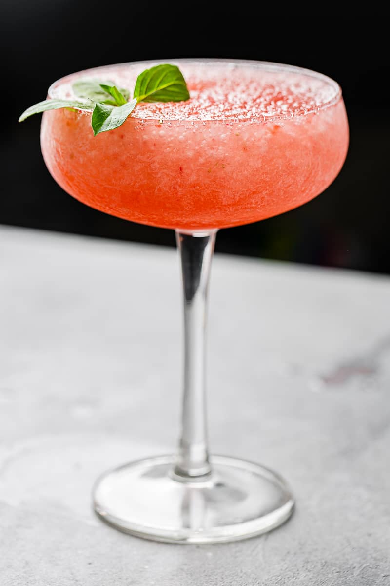 side view of backlit frozen strawberry cocktail