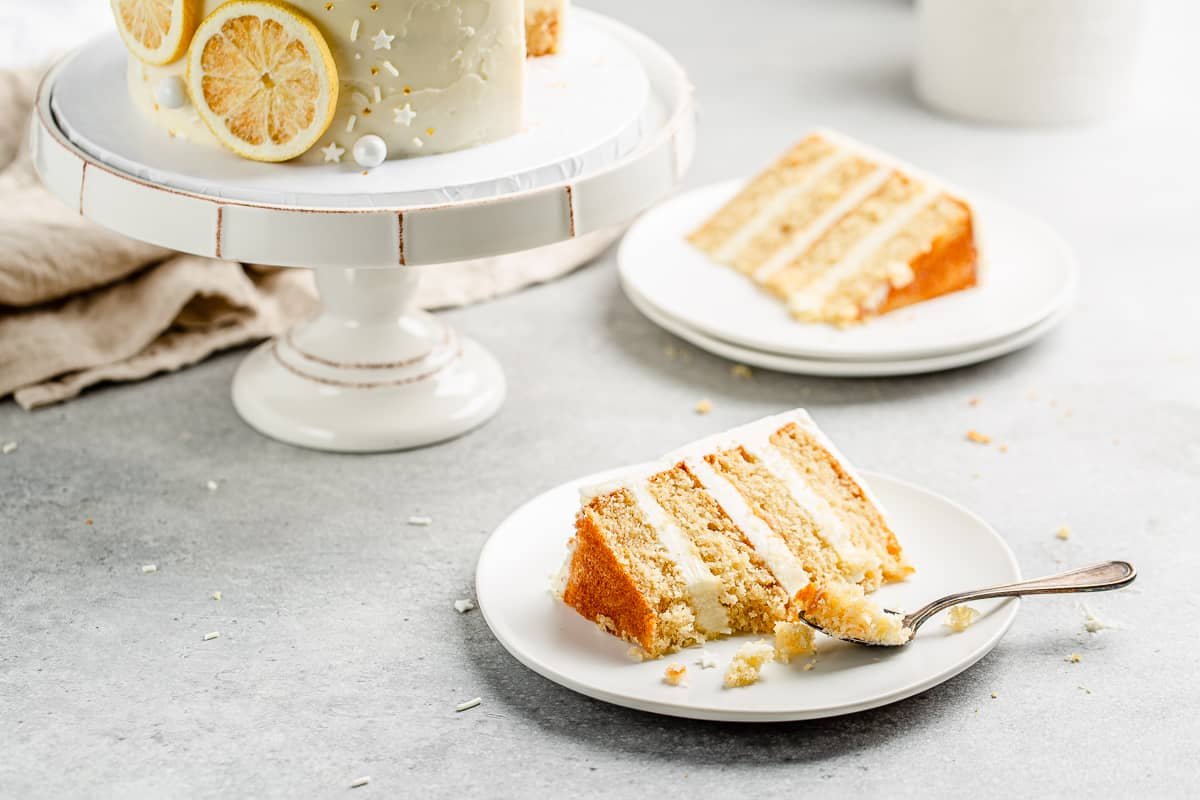 close up of a slice of the lemon layer cake with a bite of the cake on a spoon