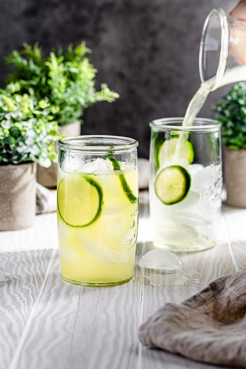 pouring pineapple limeade into serving glass that has lime wheels