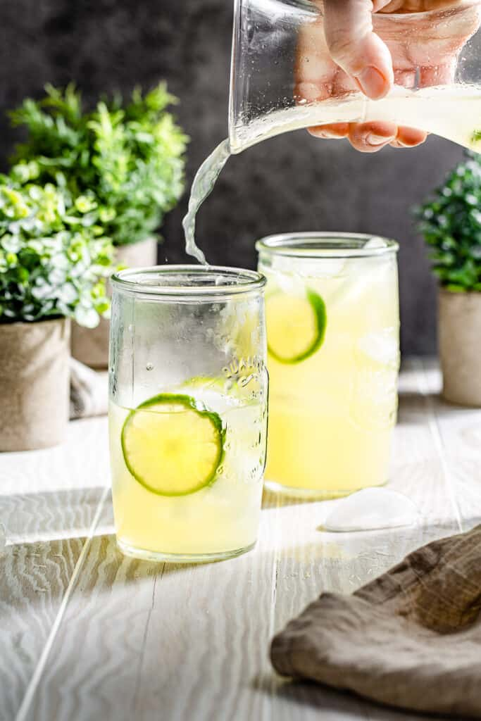limeade splashing out of a carafe into serving glass