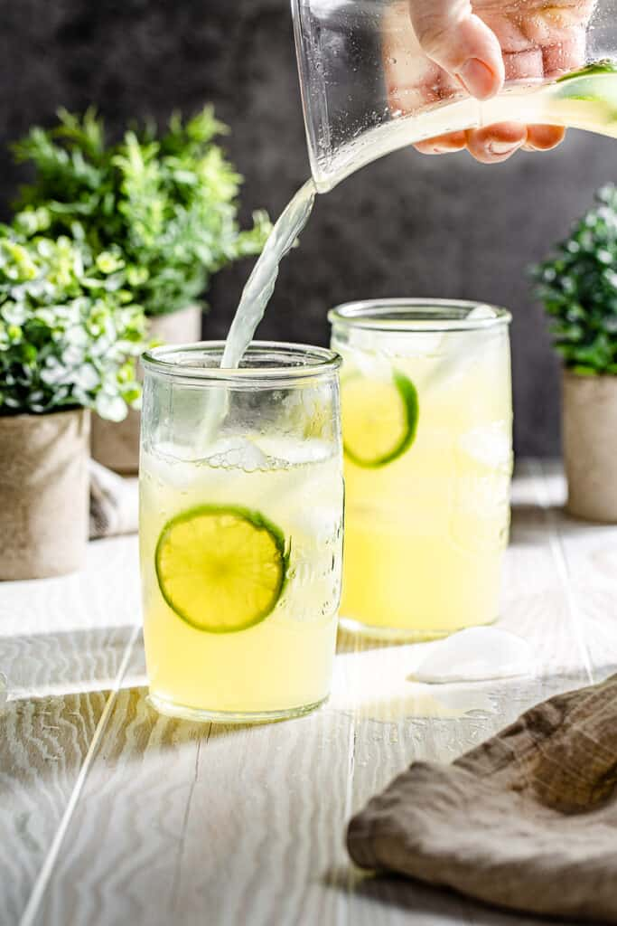 Pouring limeade into glass with lime wheel in the glass