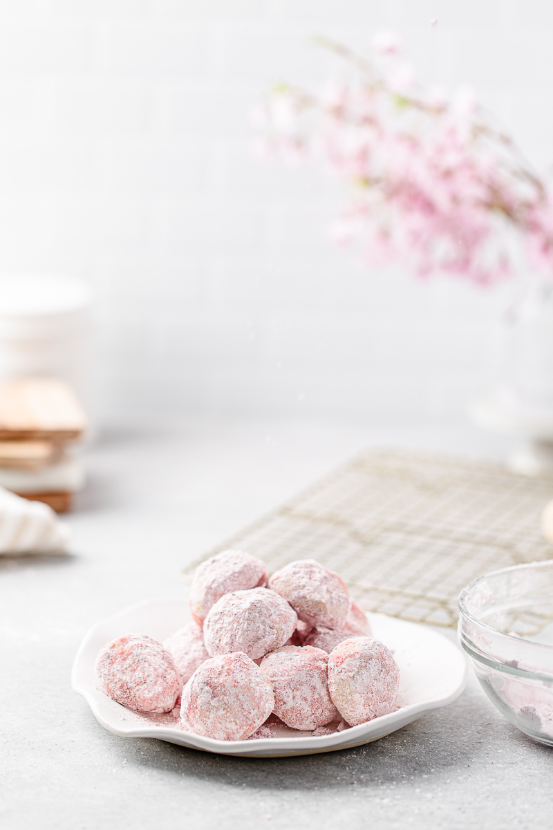 pile of pink snowball cookies on a plate with cooling rack in the background