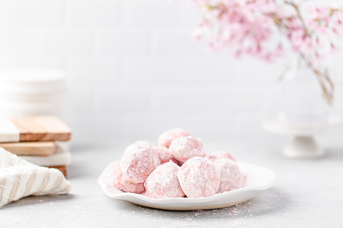 Pile of pink snowball cookies on a plate