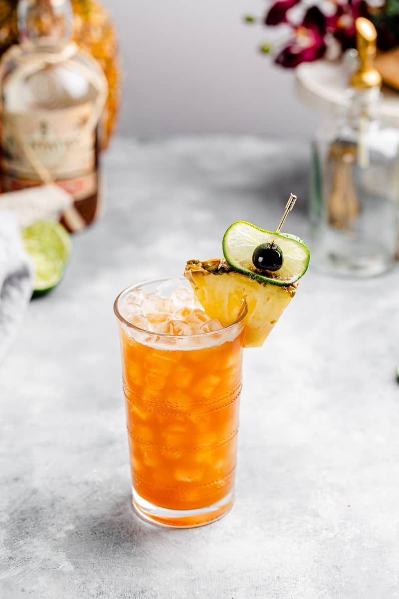 top view of a Rum and Ramazzotti cocktail with pineapple, cherry and lime garnish