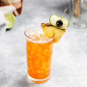 top view of a Ramazzotti Rum cocktail with pineapple, cherry and lime garnish