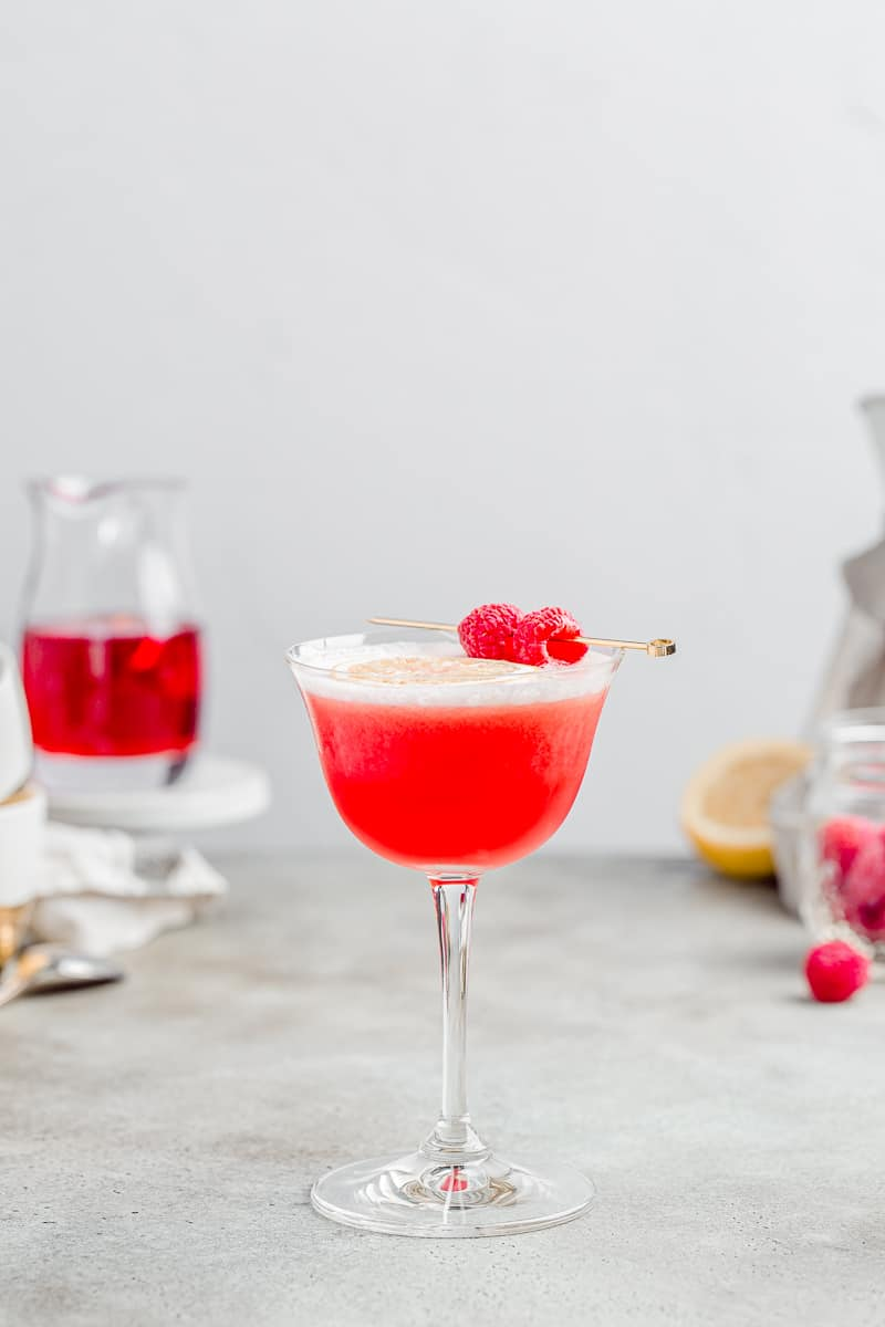 side view of red drink in sour glass with raspberries and lemon