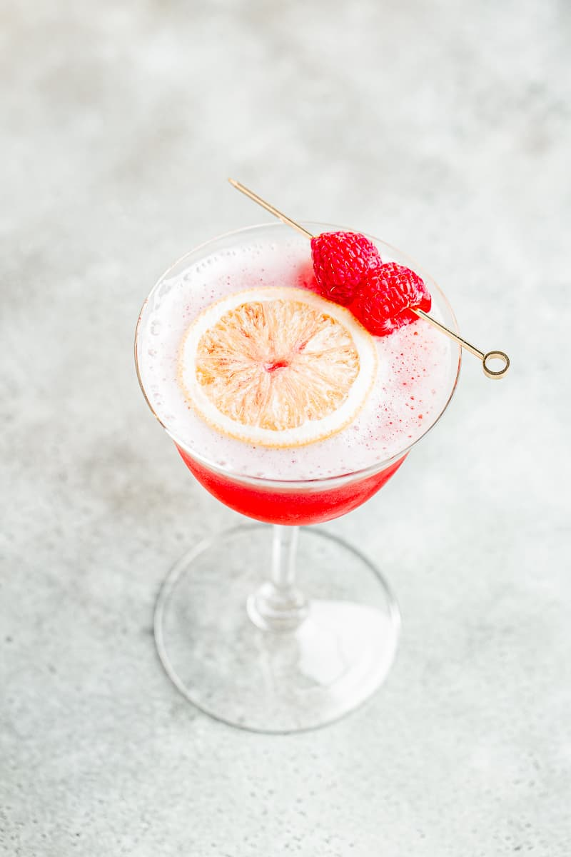 top view of the drink with a lemon wheel and raspberries
