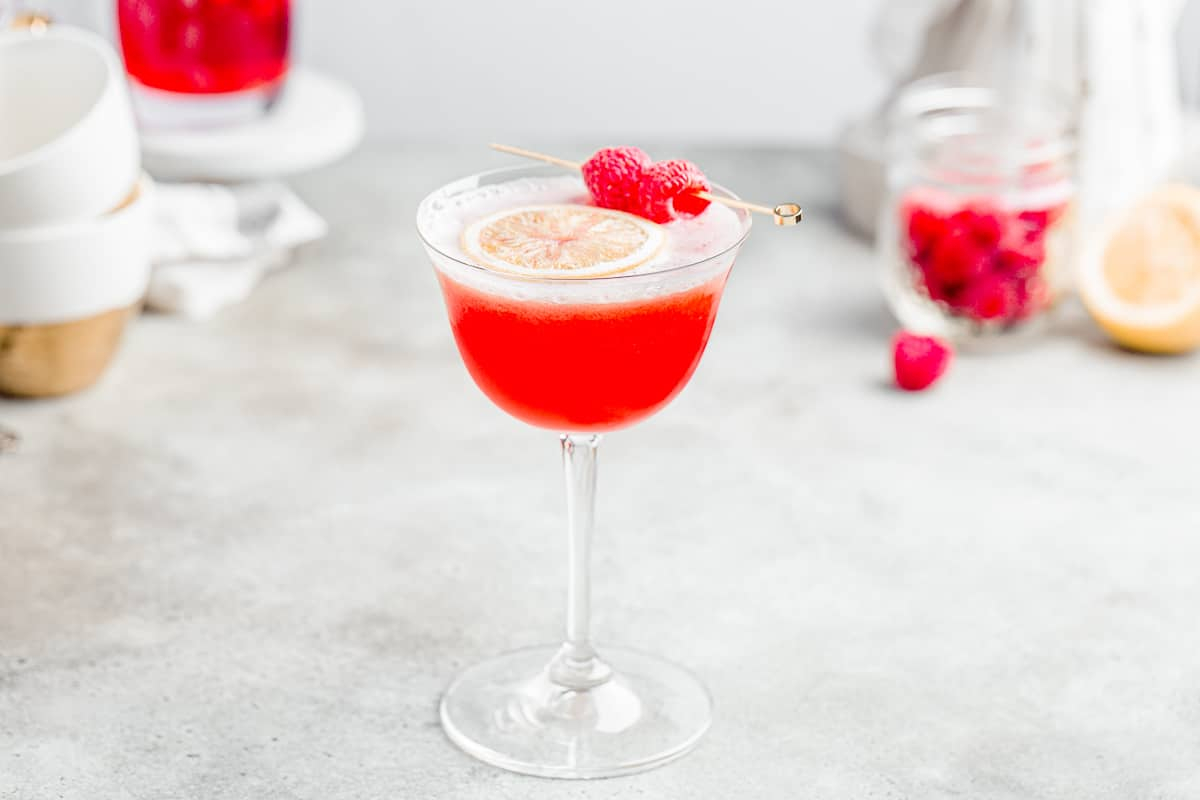 horizontal image of raspberry mocktail with teacups, raspberries, and lemons in the background