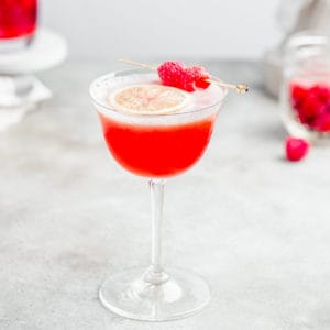 angled view of raspberry mocktail with some raspberries in the background