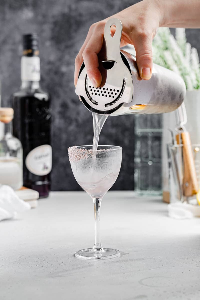 pouring cocktail into a chilled glass with a sugar rim