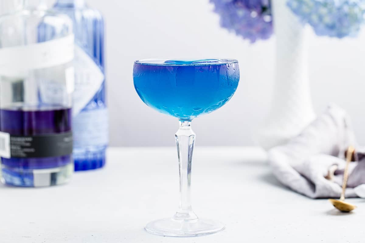 horizontal photo of blue cocktail in a coupe glass with gin bottles and flowers in the background