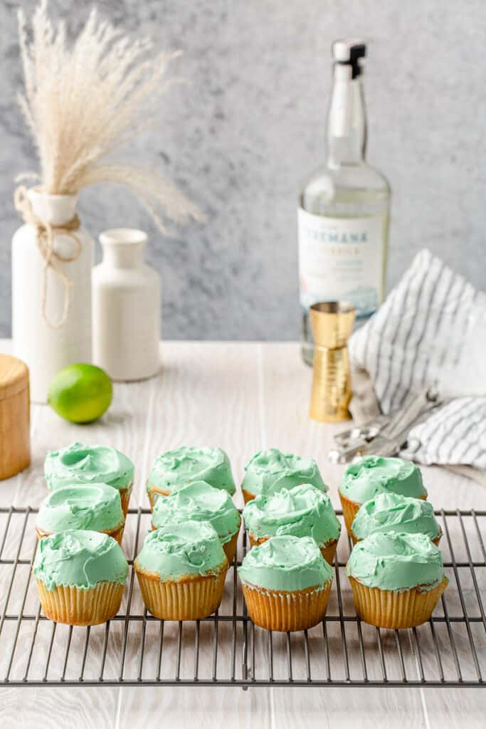 cupcakes with green frosting on a cooling rack