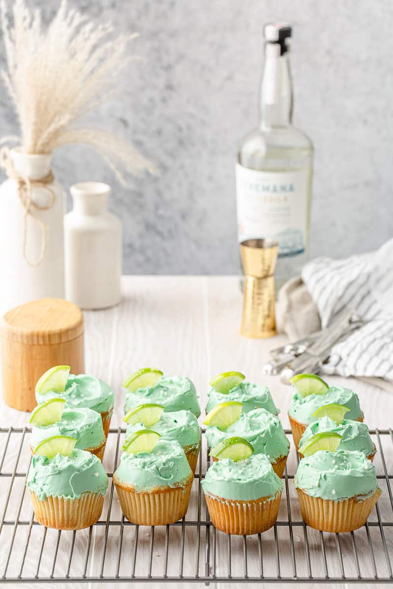rows of margarita cupcakes on a cooling rack with tequila in the background