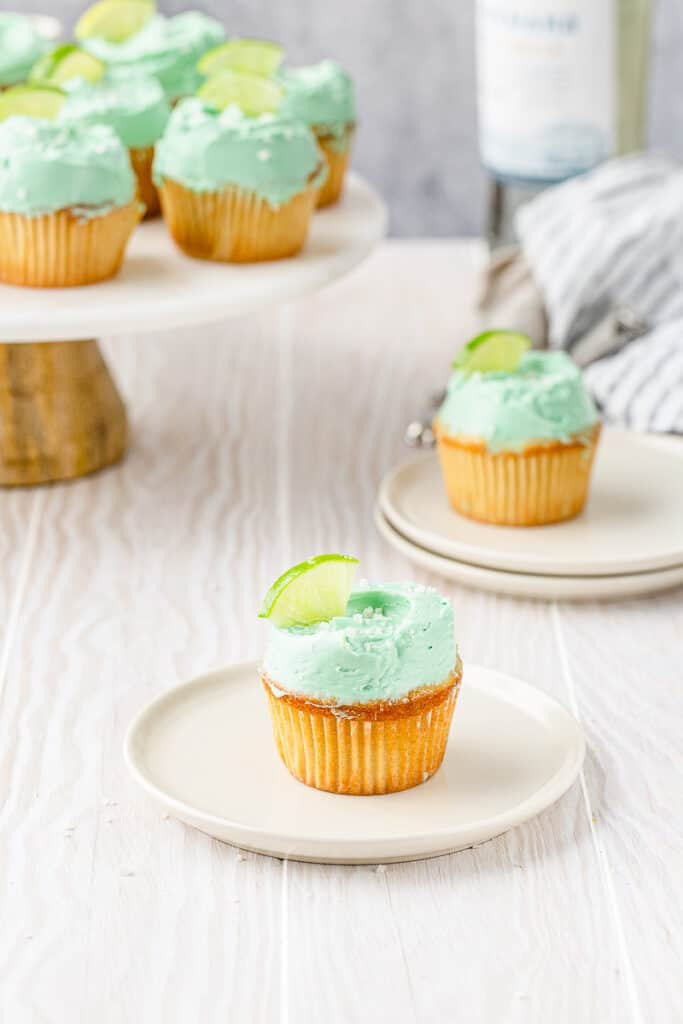 cupcake with green frosting and a lime wedge on a plate with other cupcakes in the background