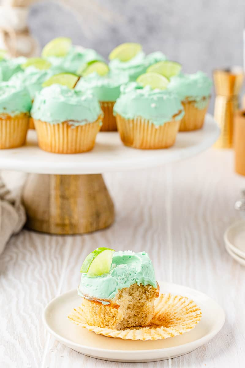 cupcake with a bite taken out of it and other cupcakes on a cake stand in the background