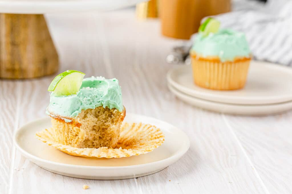 close up of a cupcake with green frosting and a bite taken out of it