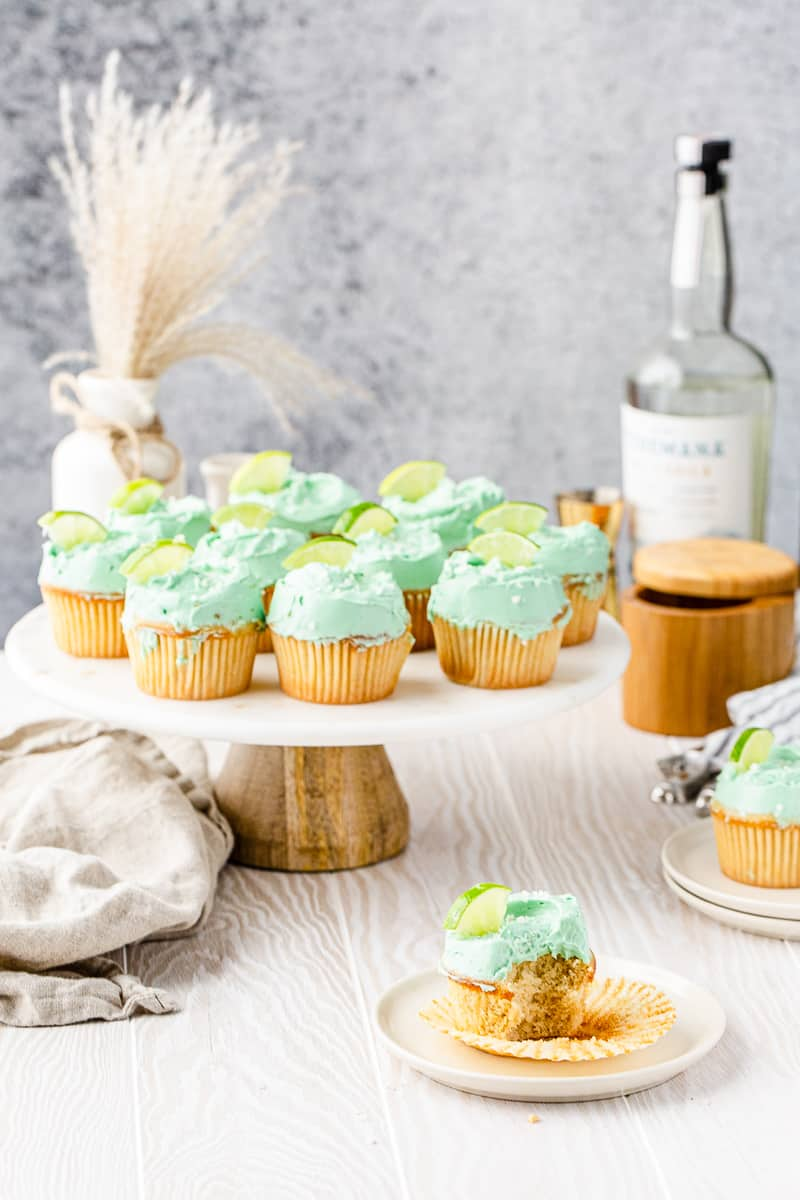 wide shot of margarita cupcakes on a cake stand with tequila in the background and a bitten cupcake in front