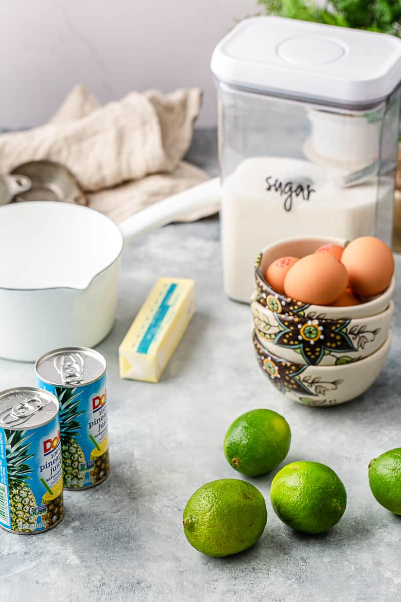 ingredients set out on the counter - limes, pineapple juice, butter, eggs, sugar