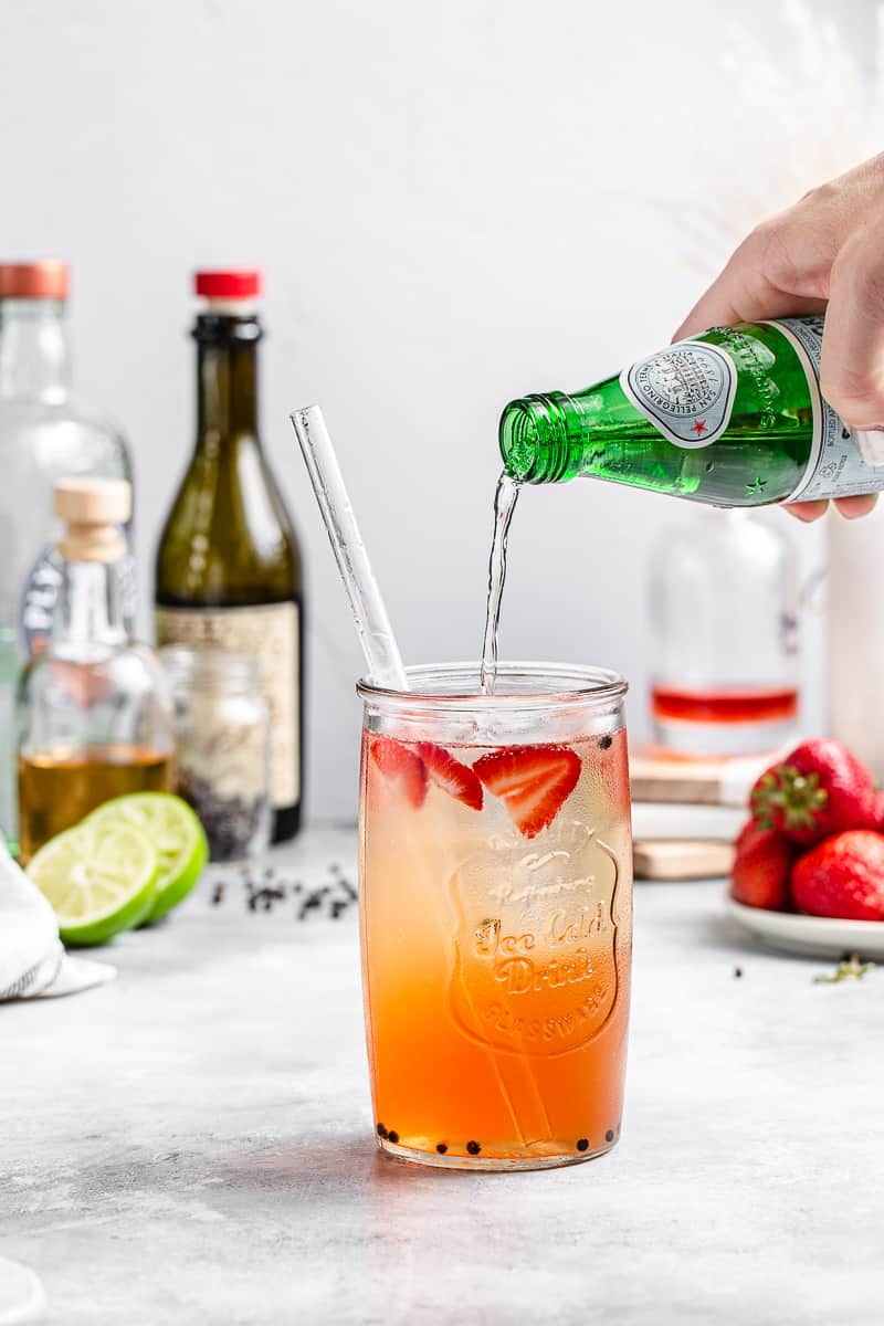 pouring seltzer into cocktail