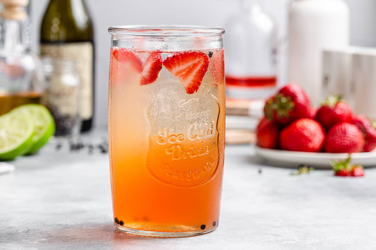 side view of strawberry cocktail with alcohol bottles and strawberries and limes