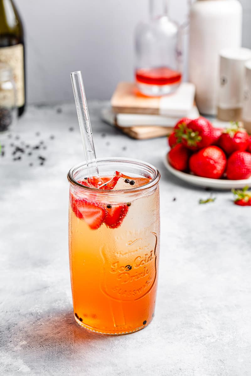 red and orange cocktail with strawberries in the background