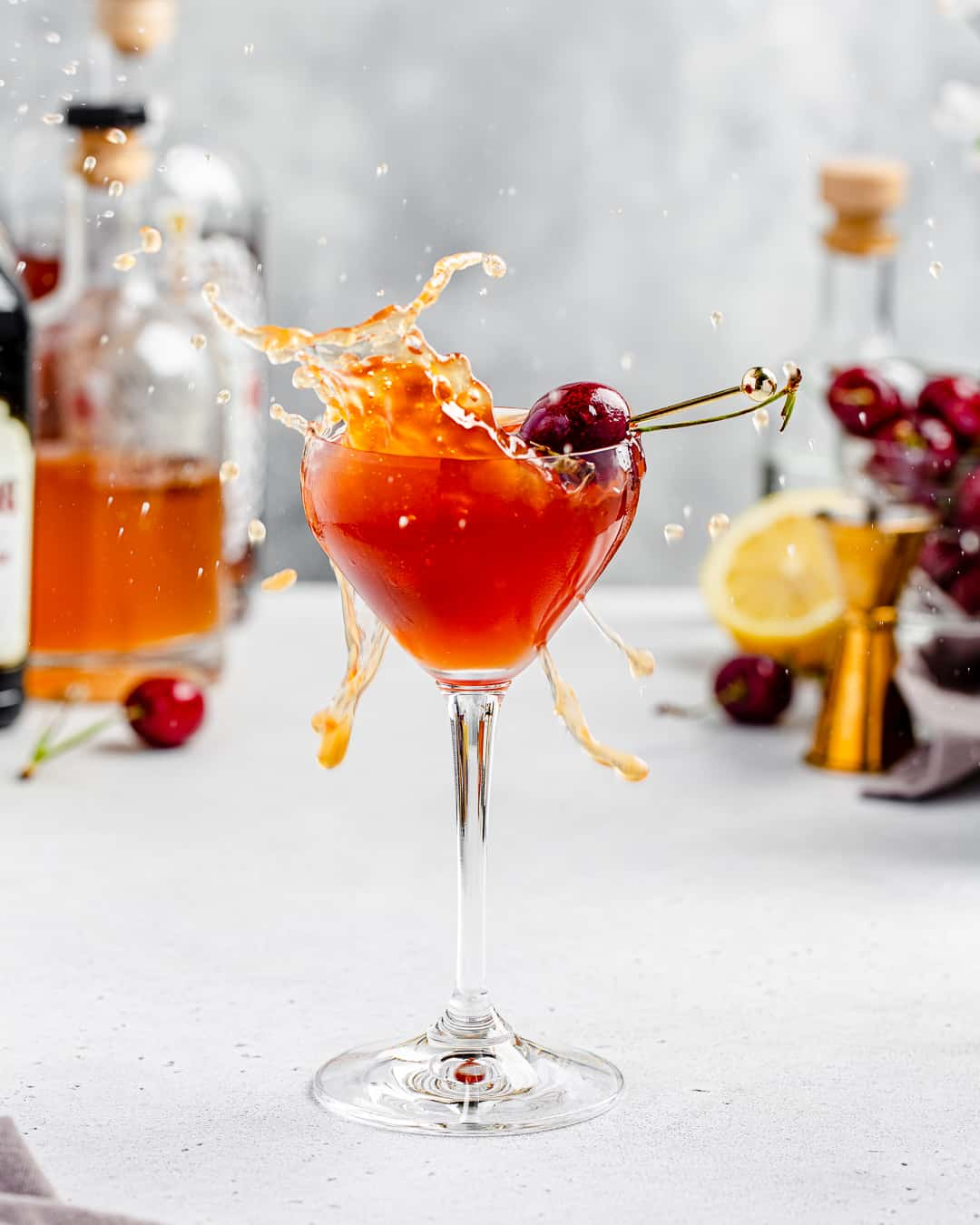 side view of cherry cocktail splashing everywhere