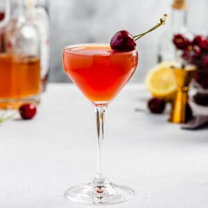 side view of cherry ginger cocktail in a nick and nora glass