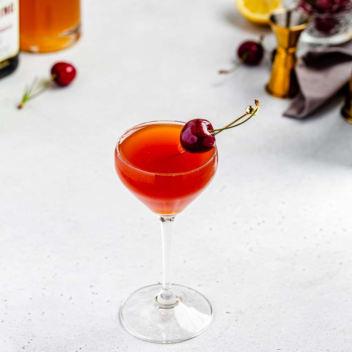 top view of cherry ginger cocktail with some bar tools in the background