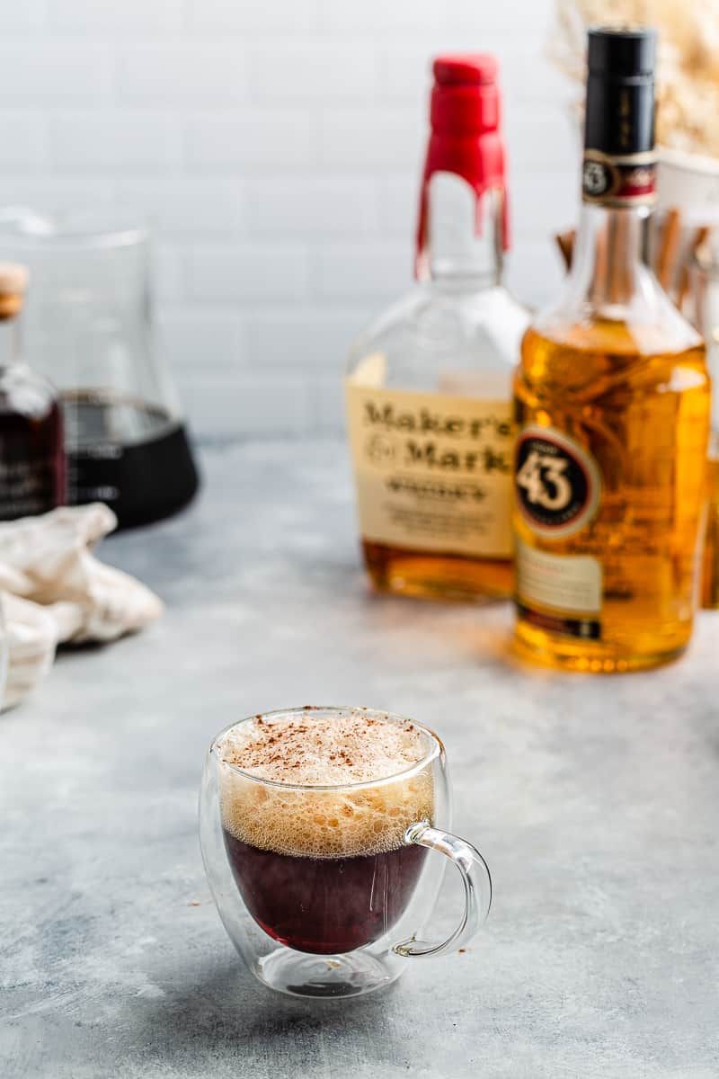 Cold Brew bourbon cocktail in a glass mug with the ingredients in the background
