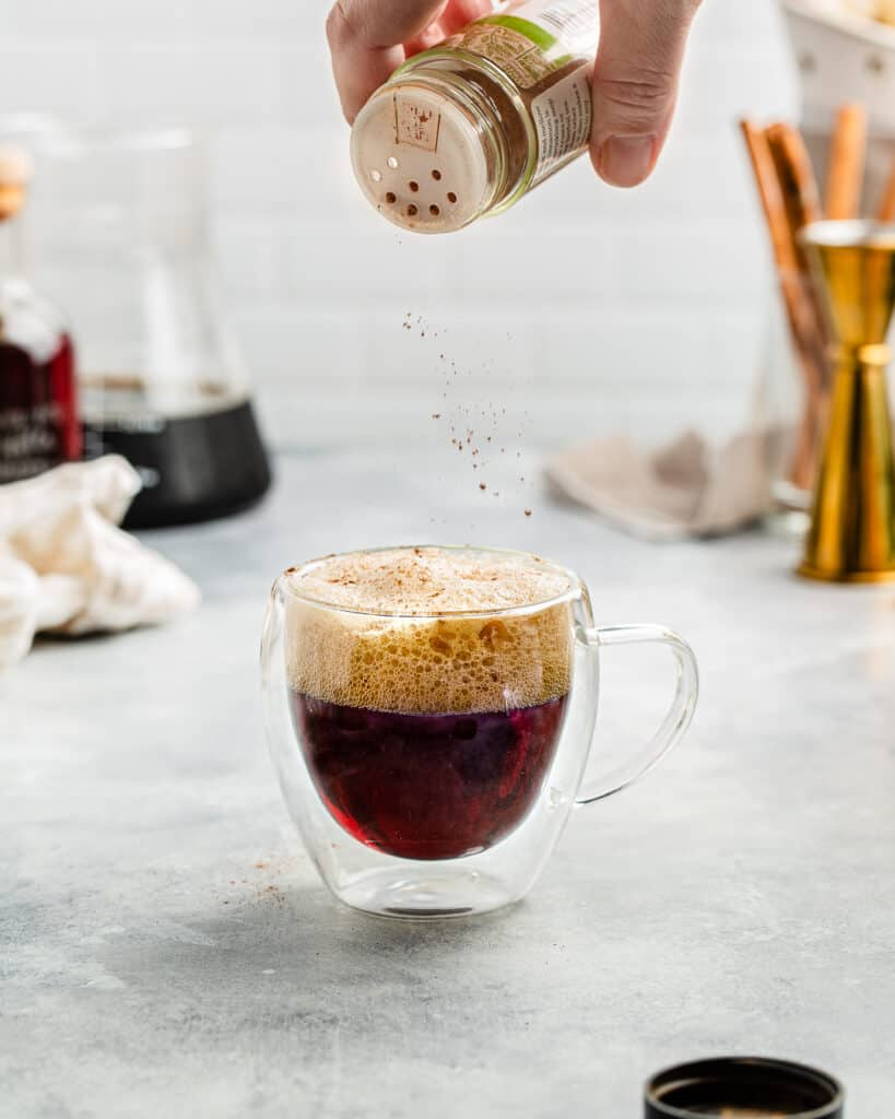 sprinkling cinnamon on top of the cocktail