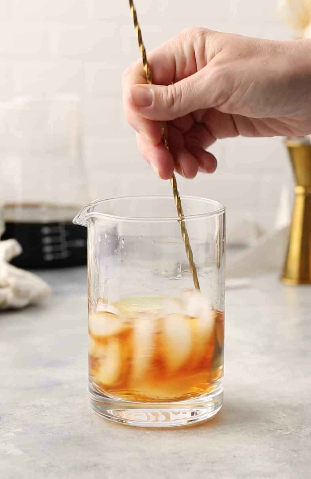 stirring the bourbon and liqueur with ice in a cocktail mixing glass