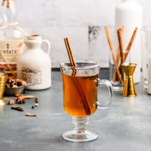hot apple cider cocktail in front with ingredients in the background