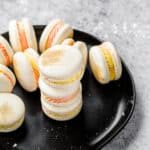 group of macarons with pink and yellow filling on a black plate