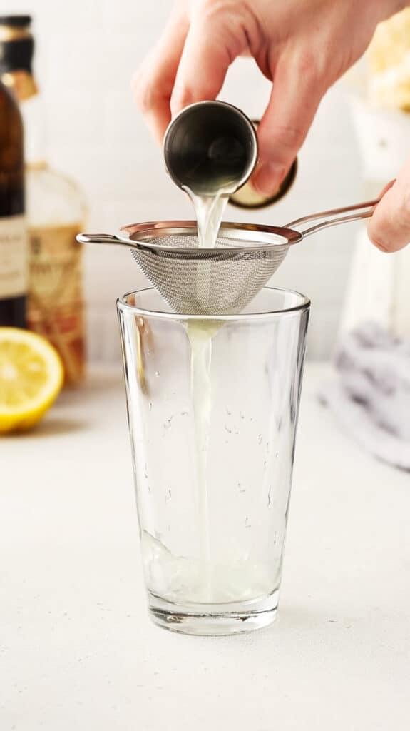 pouring lemon juice through a strainer into the cocktail mixing glass