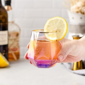 cocktail in an iridescent glass held in a hand with lemon wheel garnish